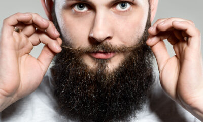 man with beard adjusting his mustaches while standing against grey background