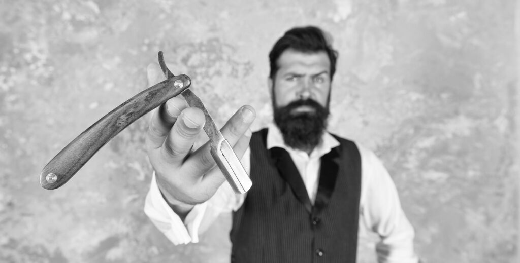Man holding out a straight razor