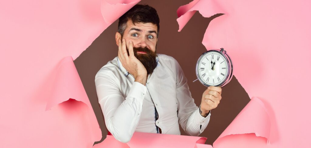 bearded man holds clock. Man is late. Looking through hole in pink paper. Losing time. Late. Deadline. Business concept. Saving time concept. Bearded man peeking through hole in pink paper.